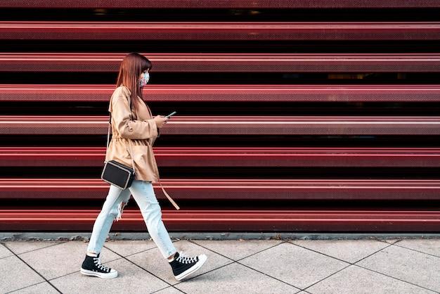 Foto conservada em estoque de uma jovem mulher caucasiana, usando seu smartphone na rua. ela está usando uma máscara devido a covid19.