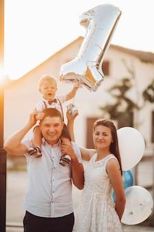 Foto conservada em estoque de uma linda família caucasiana com filho bebê segurando inflável número um. ao ar livre. bom tempo e luz solar.