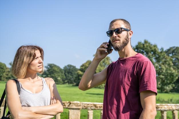 Foto conservada em estoque de uma menina com os braços cruzados, olhando para um menino com uma expressão séria que fala com o celular olhando para a frente em um jardim