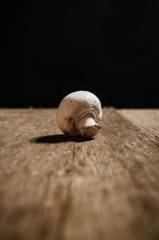 Foto conservada em estoque do único cogumelo na tabela de madeira e no fundo preto.