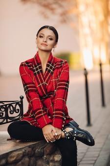 Foto conservada em estoque retrato de jovem atraente em gabardine xadrez brilhante, calça preta e botas da moda, sentado no banco no parque. olhando para a câmera com ar sonhador.