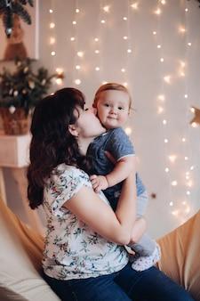 Foto conservada em estoque retrato de menino bonitinho com sua mãe sentada no balanço contra guirlanda iluminada na parede ao fundo. mãe abraçando o filho dela e olhando para a câmera. conceito de natal.