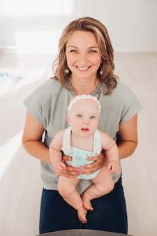 Foto conservada em estoque retrato de uma linda mãe sorridente em t-shirt cinza e jeans, segurando sua adorável filhinha nas mãos e olhando para a câmera alegremente.
