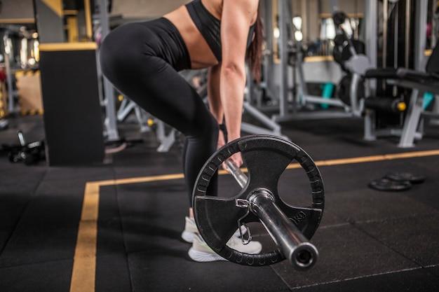 Foto cortada de uma atleta irreconhecível levantando uma barra na academia