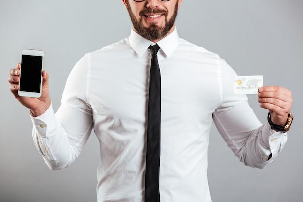 Foto cortada do homem bisinesslike de camisa e gravata, apresentando telefone inteligente e cartão de crédito, isolado sobre a parede cinza
