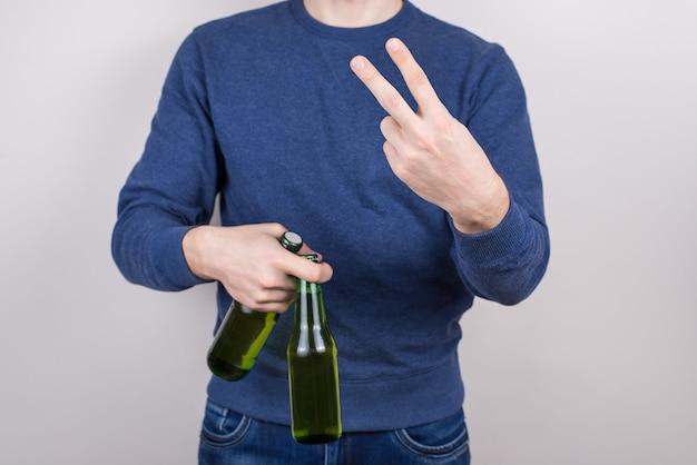 Foto cortada em close de um cara positivo bonito e satisfeito fazendo o símbolo de v para a câmera segurando duas cervejas frescas em um fundo cinza isolado na palma da mão