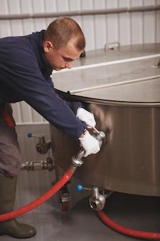 Foto cortada vertical de um trabalhador de manutenção consertando um tanque de cerveja de fermentação em uma fábrica de cerveja artesanal