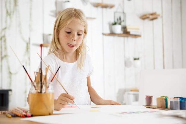 Foto da adorável menina loira com sardas, mordendo a língua por causa da inspiração durante a pintura. garota com cabelos loiros, sentado na sala cheia de luz da manhã e vestindo roupas brancas.