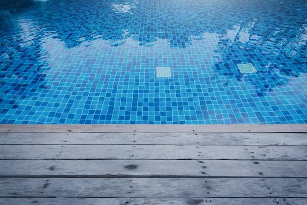 Foto da água em uma piscina com reflexões ensolaradas e a passagem de madeira.