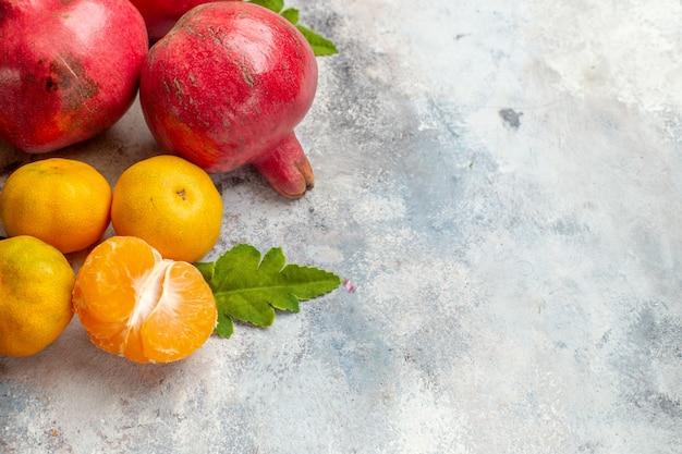 Foto da árvore de frutas com sabor de vitamina de tangerinas frescas com romãs vermelhas em fundo claro