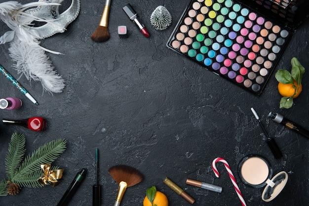 Foto da árvore de natal, tangerina, pincéis, batom, paleta com sombras na mesa preta com espaço para texto no centro