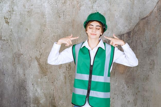 Foto da bela arquiteta com capacete verde apontando