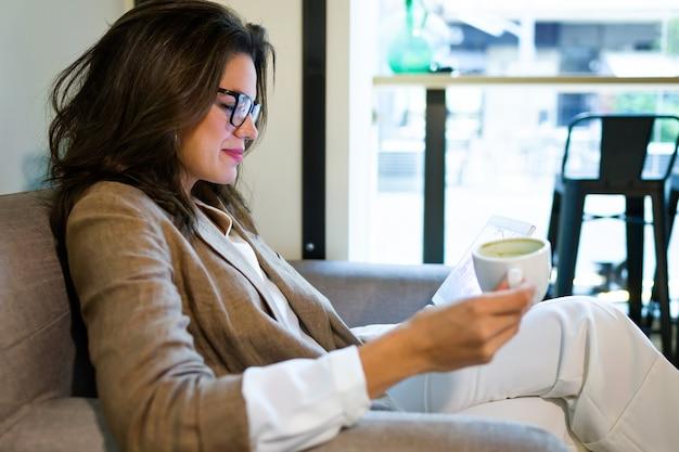 Foto da bela jovem empresária trabalhando com seu tablet digital no café.