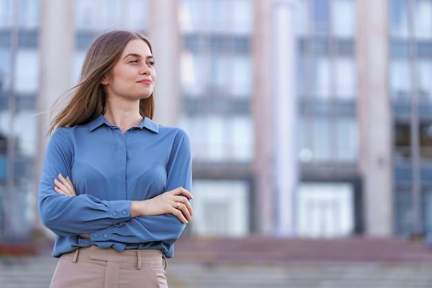 Foto da bela jovem empresária vestindo camisa de chiffon azul em pé no prédio na rua com os braços cruzados.