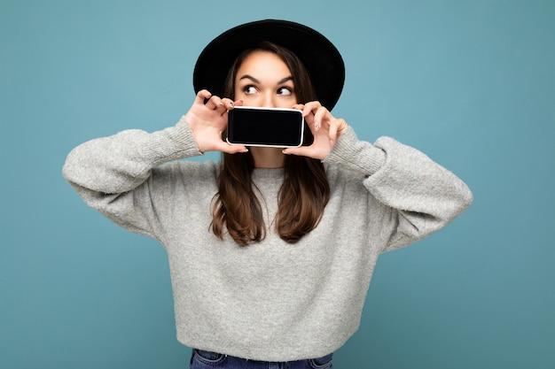 Foto da bela jovem positiva usando chapéu preto e suéter cinza segurando o celular, mostrando o smartphone isolado no fundo, olhando para a câmera.