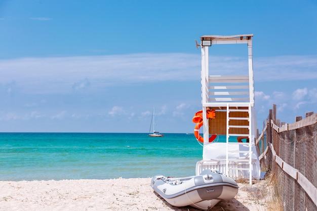 Foto da bela praia tropical em um dia ensolarado de verão, com um local de salva-vidas e barco estacionado à beira-mar
