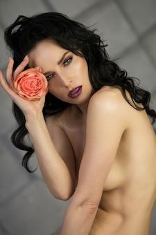 Foto da beleza de uma mulher elegante posando de topless com uma rosa