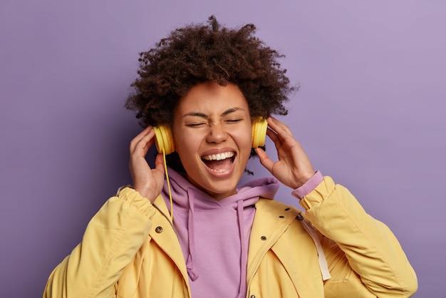 Foto da cabeça de um adolescente afro-americano alegre e cacheado usando fones de ouvido para cancelar o ruído, ouve uma lista de reprodução de música positiva e abre a boca amplamente