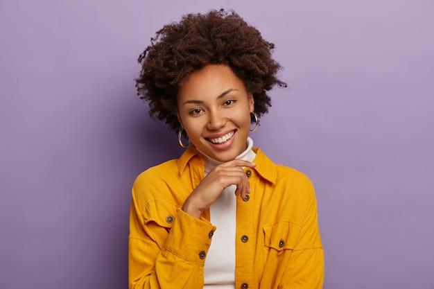 Foto da cabeça de um adulto adorável e feliz sorri agradavelmente, mostra os dentes brancos, mantém a mão sob o queixo, usa uma jaqueta amarela elegante, expressa boas emoções, tem uma aparência entusiasmada, está de bom humor