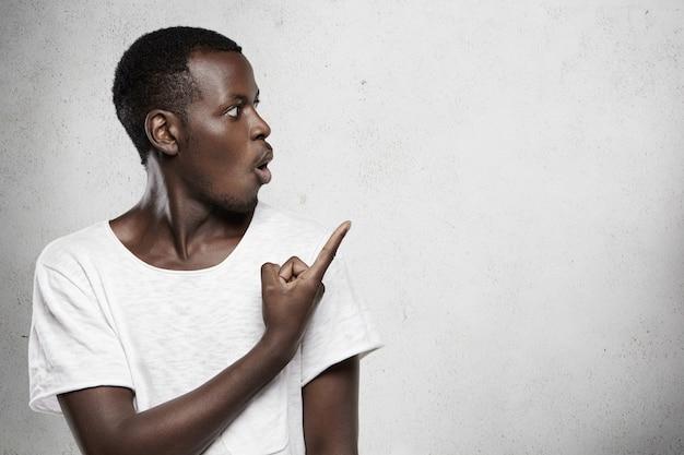 Foto da cabeça de um cliente de pele escura surpreso vestido com uma camiseta branca parecendo em estado de choque, apontando o dedo para uma parede em branco com espaço de cópia para seu texto ou conteúdo publicitário, exclamando: olha só!