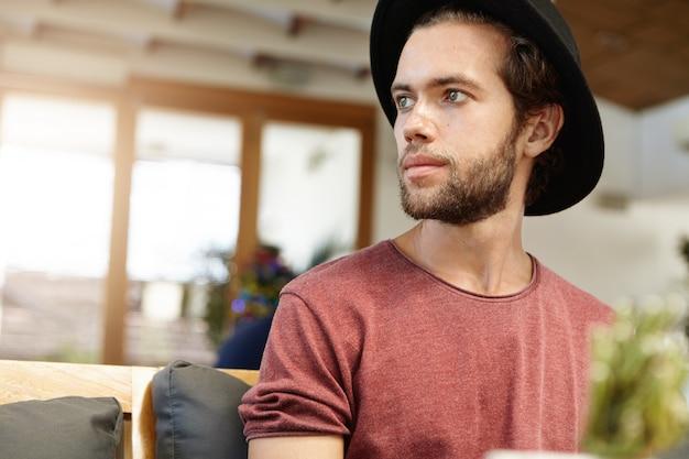 Foto da cabeça de um jovem e bonito modelo com barba difusa em um headwear estiloso e uma camiseta com mangas arregaçadas olhando para longe enquanto posa dentro de casa