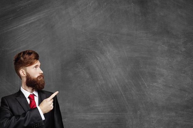 Foto da cabeça de um jovem trabalhador de escritório ou empresário elegante, com barba espessa, vestido com roupa formal, olhando para um quadro-negro em branco e apontando para o espaço de cópia para seu texto ou conteúdo promocional