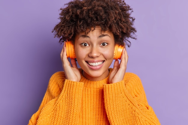 Foto da cabeça de uma garota afro-americana muito alegre com cabelo encaracolado segurando fones de ouvido com sorrisos e usando poses de suéter tricotado