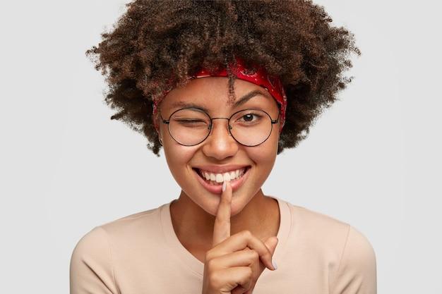 Foto da cabeça de uma jovem afro brincalhona alegre fazendo um gesto de silêncio com uma expressão positiva, pisca os olhos