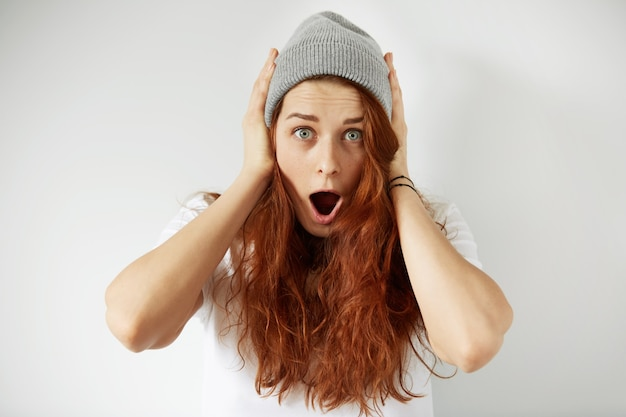 Foto da cabeça de uma linda garota ruiva de camiseta branca e boné cinza olhando com surpresa
