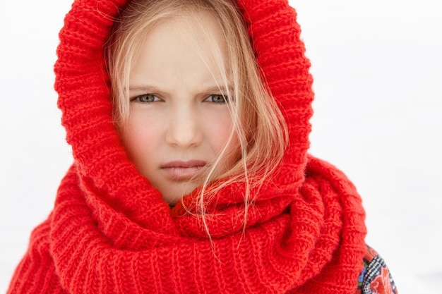 Foto da cabeça de uma linda garotinha loira caucasiana usando um lenço de lã vermelho na cabeça e no pescoço