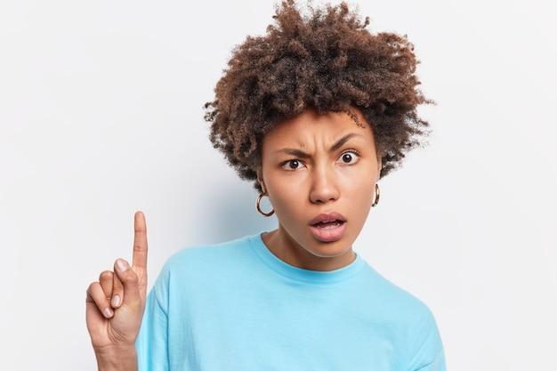 Foto da cabeça de uma mulher afro-americana de cabelos cacheados descontente parece confusa indica que o dedo indicador acima mostra algo incrível vestida com uma camiseta azul casula isolada sobre uma parede branca