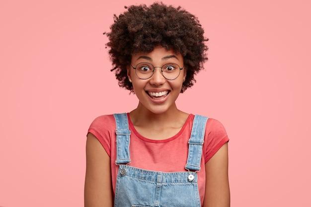 Foto da cabeça de uma mulher afro-americana feliz usando camiseta e macacão jeans