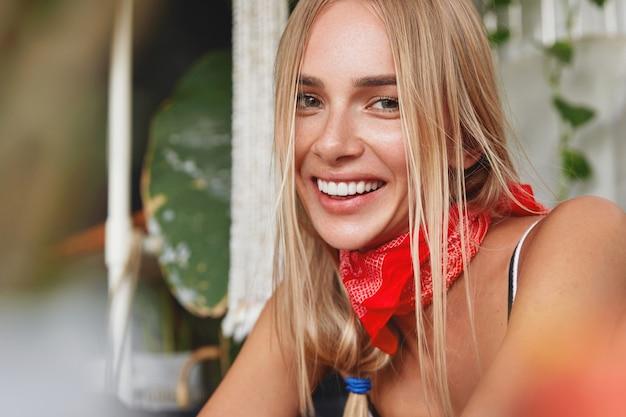 Foto da cabeça de uma mulher loira atraente e satisfeita com expressão positiva e sorriso largo
