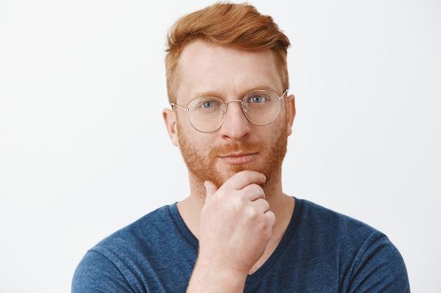 Foto da cabeça do cara ruivo bonito, criativo e inteligente, com cerdas nos óculos e camiseta azul, esfregando a barba no queixo e olhando com um sorriso malicioso, tendo um ótimo plano ou ideia sobre a parede cinza