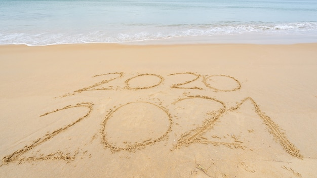 Foto da chegada do texto de ano novo de 2021 e da partida do ano de 2020 com texto de letras na praia com ondas