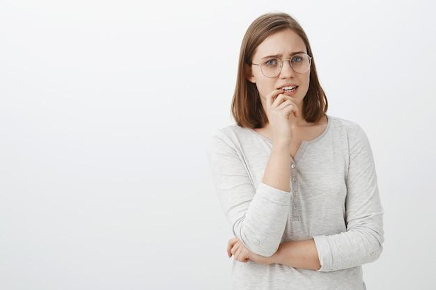 Foto da cintura de preocupada com uma fofa mulher europeia de óculos e blusa segurando o dedo no lábio, franzindo a testa, parecendo nervosa e preocupada esperando notícias do hospital de mãos cruzadas no corpo