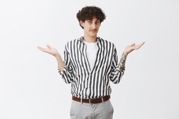 Foto da cintura de um cara desavisado, bonito e engraçado, desavisado, com bigode e cabelo escuro encaracolado, encolhendo os ombros com as palmas das mãos abertas, sem ter a menor ideia de como se comportar ou qual resposta