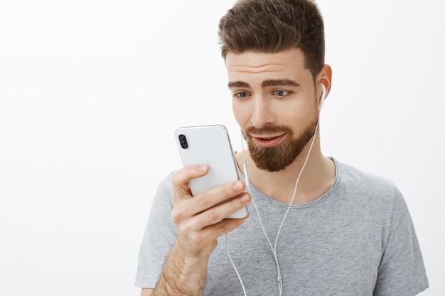 Foto da cintura de um homem barbudo encantador e fofo com olhos azuis usando fones de ouvido segurando o smartphone perto do rosto enquanto lê ou assiste a um vídeo encantador olhando para o celular encantado