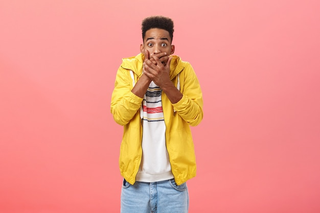 Foto da cintura de um jovem estudante moreno de pele escura chocado e chocado em uma roupa estilosa cobrindo a boca com as palmas das mãos tremendo e estupor, posando sobre um fundo rosa