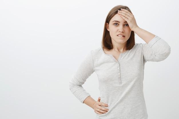 Foto da cintura de uma colega de trabalho inteligente e criativa com blusa branca segurando a mão na testa, mordendo o lábio inferior, preocupada e preocupada, enfrentando uma situação difícil, tentando encontrar uma solução sobre a parede cinza