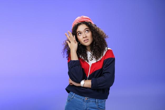 Foto da cintura de uma garota legal arrogante, entediada e assertiva entediada em roupa de streetstyle revirando os olhos, fazendo facepalm e fazendo careta de irritação e decepção, posando contra um fundo azul.