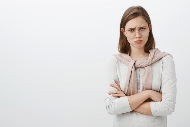 Foto da cintura de uma garota triste, infeliz e sombria, com a orelha abaulada, franzindo a testa e carrancuda, cruzando os braços sobre o corpo, sentindo ciúmes ou arrependimento de ter sido punido pelos pais que estão chateados sobre a parede cinza