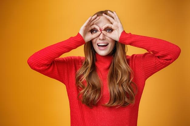 Foto da cintura de uma menina ruiva engraçada infantil e brincalhona em um vestido de tricô vermelho fazendo caretas mostrando círculos sobre os olhos como óculos de proteção e sorrindo amplamente se divertindo contra um fundo laranja como uma criança