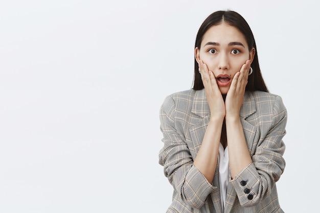 Foto da cintura de uma mulher fofa atordoada e muda em um casaco da moda sobre uma camiseta branca, ofegando, olhando surpreso e impressionado, segurando as palmas das mãos nas bochechas, sendo espantado com os rumores