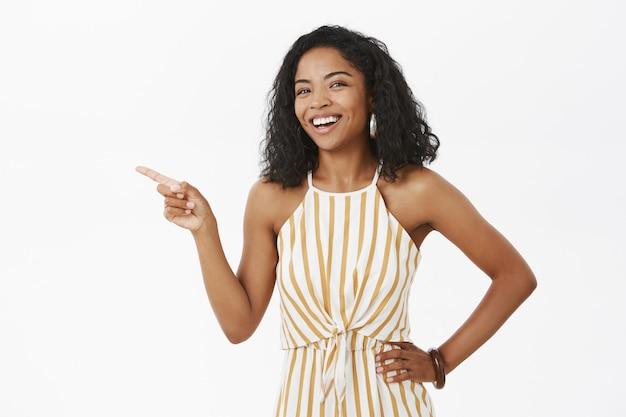 Foto da cintura para cima da despreocupada e charmosa senhora de pele escura bem-sucedida com penteado encaracolado em um macacão amarelo estiloso segurando a mão na cintura