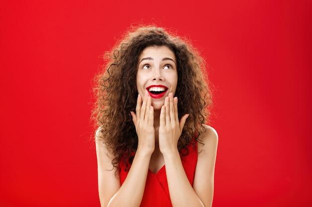 Foto da cintura para cima da divertida e entretida jovem feliz e sonhadora namorada em um vestido estiloso, segurando as palmas das mãos no queixo e abrindo a boca com um largo sorriso, parecendo encantado como se estivesse vendo um milagre sobre a parede vermelha.