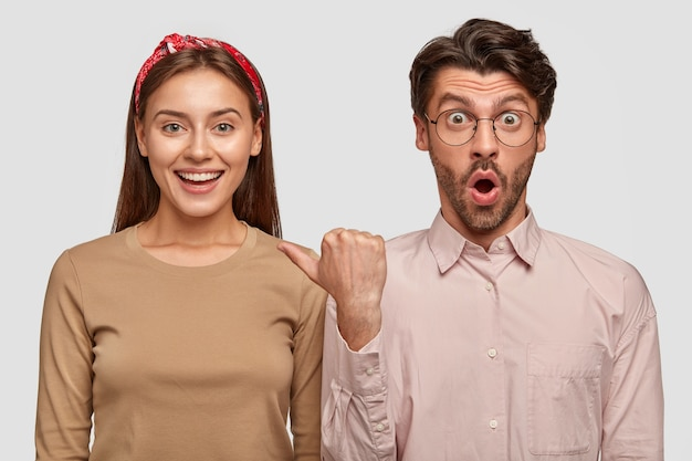 Foto da cintura para cima da jovem esposa alegre e do marido estupefato