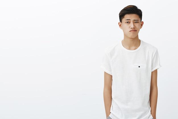 Foto da cintura para cima de um cara coreano elegante e bonito em uma camiseta branca de mãos dadas nos bolsos sorrindo de pé em pose normal, perdendo tempo