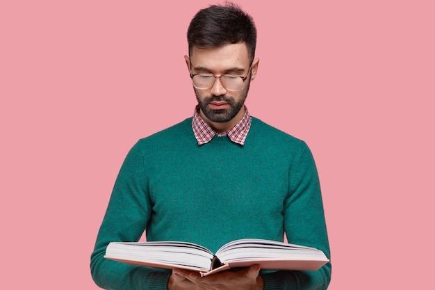 Foto da cintura para cima de um jovem sério com a barba por fazer obtém conhecimento de um livro científico, usa óculos para uma boa visão, sendo um aluno diligente