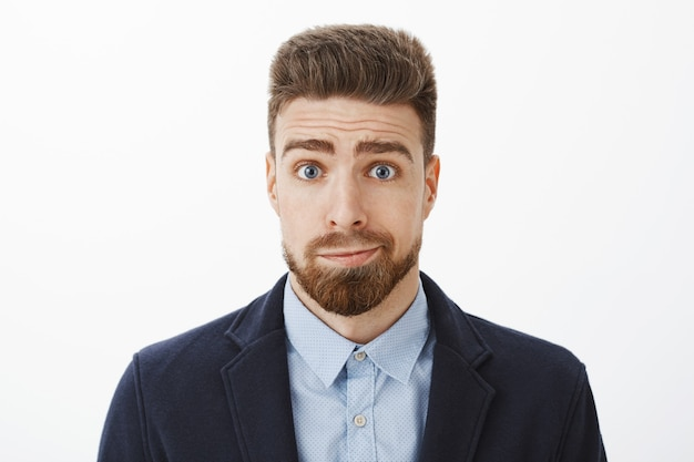 Foto da cintura para cima de um namorado moreno bobo e sombrio fofo com olhos azuis e barba sorrindo, em um terno elegante, desculpando-se por ser estúpido posando contra uma parede cinza